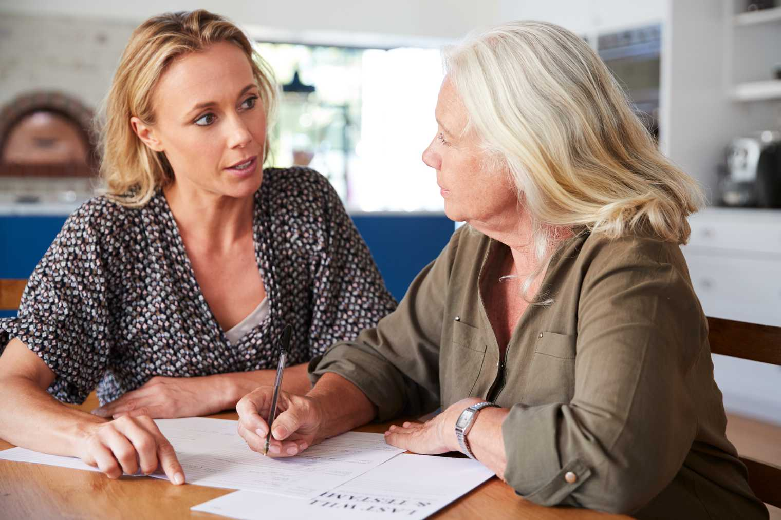 Female friend helping senior woman to complete last will and testament